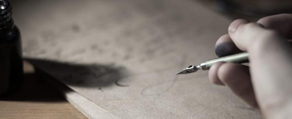 Person hält eine Schreibfeder