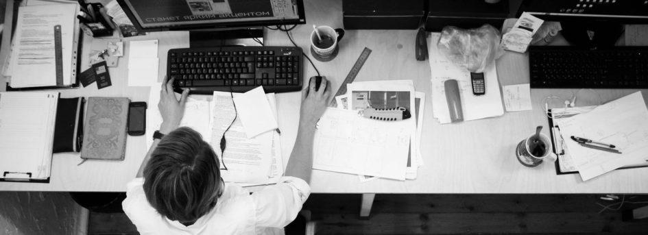 Mythos Multitasking - schwarz-weiß Foto eines vollen Schreibtisches