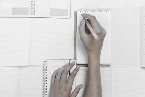 Hand schreibt auf Notizblock; Grundlagen des Selbstmanagements