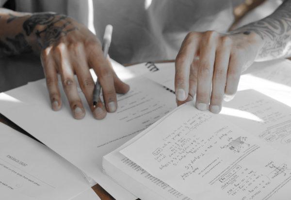 Hände mit Stift und Notizbücher
